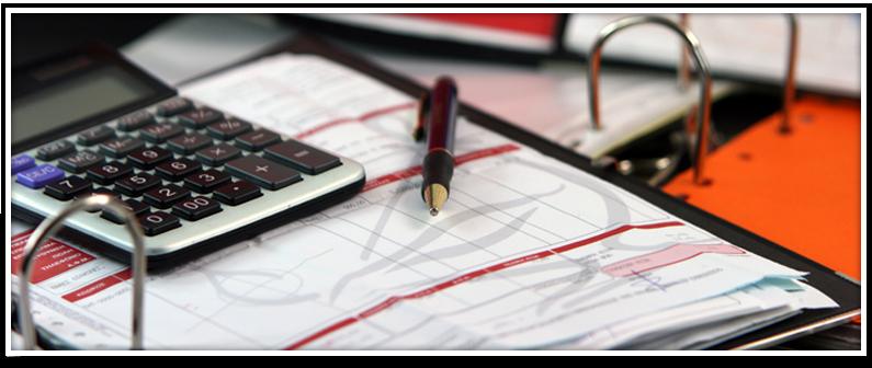 Mesa de trabajo con una calculadora, un bolígrafo y unas gráficas